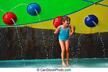 Little girl having fun in Cairns Esplanade public water park...