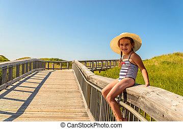 Little girl having fun on boardwalk to Brackley Beach