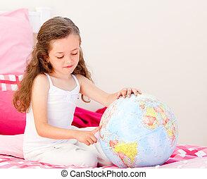 Little girl having fun on her bed