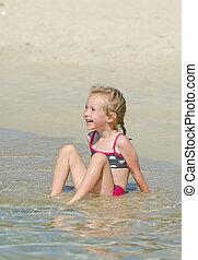 Little girl having fun on the beach.
