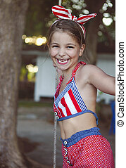 Little girl having fun on tire swing on summer day