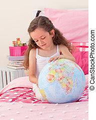 Little girl having fun with a terrestrial globe