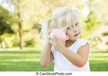 Little Girl Having Fun with Her Piggy Bank Outside