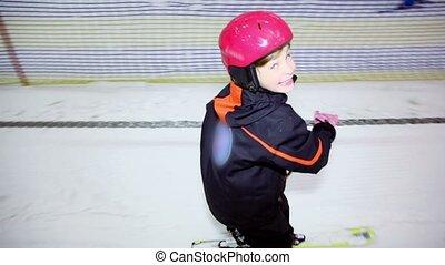 Little girl helmet holds rope and slide on ski