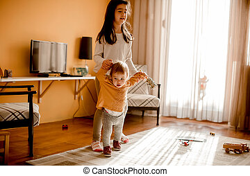 Little girl helping baby sister to walk