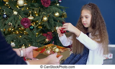 Little girl helping decorating the Christmas tree - Positive...