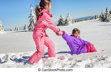 Little girl helping her friend to get up on the snow