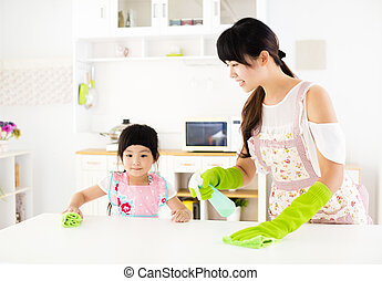 little girl helping her mother clean table in the kitchen