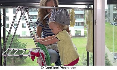 Little girl helping her mother woman to hang washed laundry