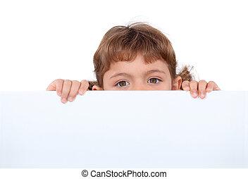 little girl hiding behind a board