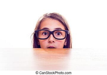 little girl hiding behind a table