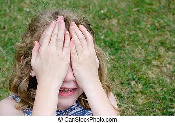 Little girl hiding face behind hands