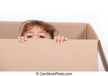 little girl hiding in a cardboard