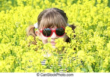 little girl hiding in flowers - little girl hiding in yellow...