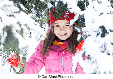 little girl hiding in pine tree. sister standing on snow under branches and smiling