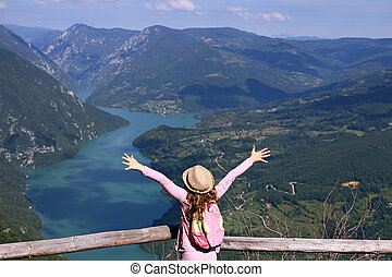 little girl hiker with hands up on mountain viewpoint