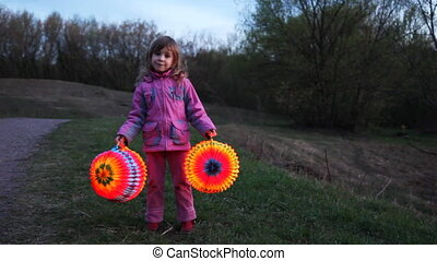 little girl hold and raise two balls from paper at night -...