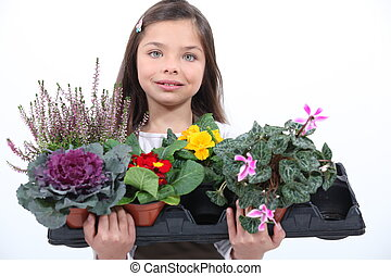 Little girl holding a bunch of flowers.