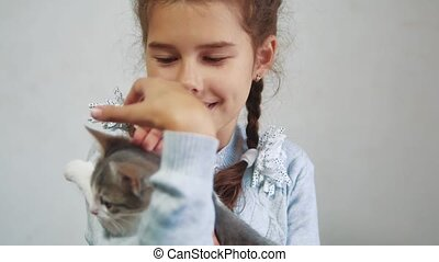 little girl holding a cat in her arms. kosh and girl pet friendship care and love. children and pets cat concept lifestyle