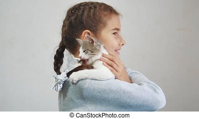little girl holding a cat in her arms. kosh and girl pet friendship care and love. children and pets cat lifestyle concept