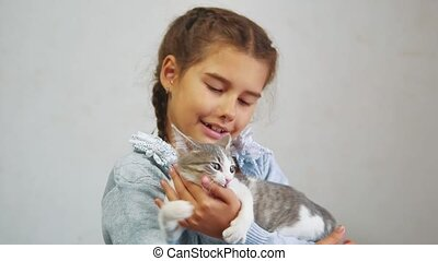 little girl holding a cat in her arms. kosh and girl pet friendship care and love. children and lifestyle pets cat concept
