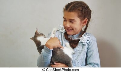little girl holding a cat in her arms. kosh and girl pet friendship care and love. children lifestyle and pets cat concept