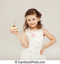 Little girl holding a delicious cake with cherry