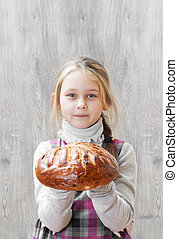 little girl holding a loaf of bread