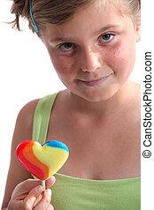 little girl holding a lollipop