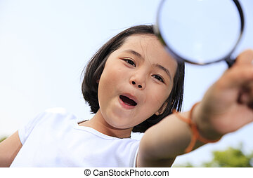 Little girl holding a magnifying glass