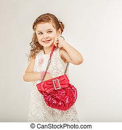 little girl holding a pink handbag