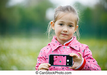 Pensive little girl holding a smart phone with a picture of her jacket on phone display, giving an image of translucency. Background picture, see-through concept.