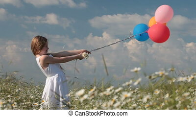 little girl holding balloons on the wind in lush summer field