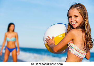 Little girl holding beach ball with mother in background.