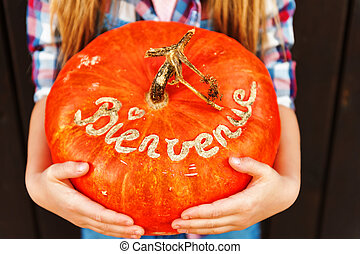Little girl holding big pumpkin with french sign Bienvenue (welcome)