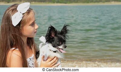 Little girl holding chihuahua pet dog in her hands