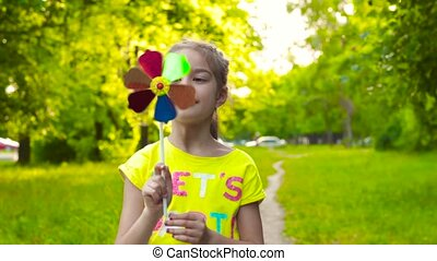 Little girl holding colorful pinwheel - Girl in colorful...