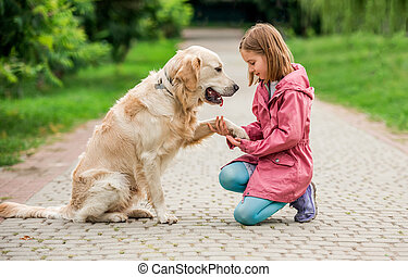 Little girl holding dog's paw in park