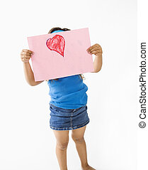Little girl holding drawing.