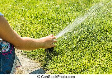 Little girl holding during irrigation, spray