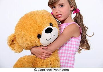Little girl holding giant teddy bear