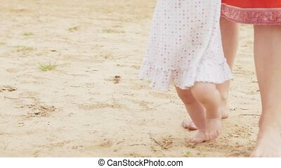 Little girl holding her mother's hand and learning to walk...