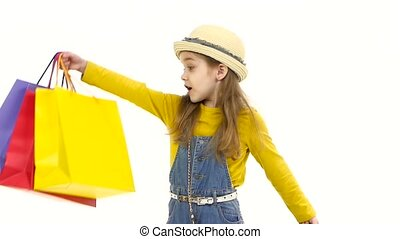 Little girl holding her purchases and surprised them. White background. Slow motion