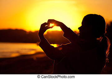 little girl holding in hands the setting sun
