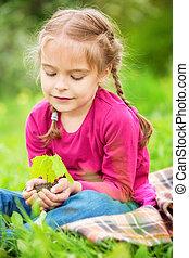 Little girl holding little green plant in her hands