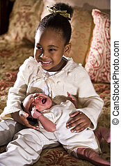Little girl holding newborn sibling - Grinning four year old...