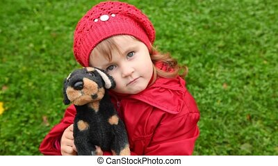 little girl holding on hands toy dog outdoor