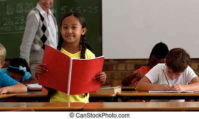 Little girl holding red notepad smiling at camera in...