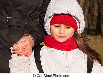 girl holding the hand of mother