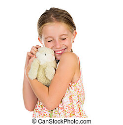 little girl holding toy bunny with her eyes squinted